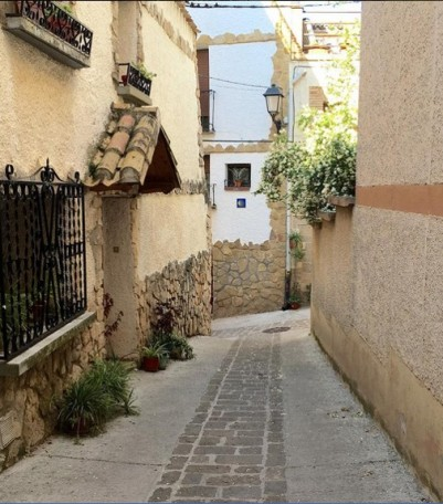 A narrow village walkway. On the wall in front is a ceramic trail marker, pointing to the left.